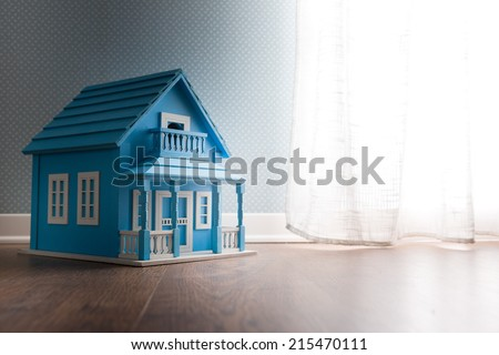 Blue wooden model house next to a window with curtain on wooden floor. - stock photo
