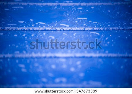 blue wooden planks with water and rain drops on the surface - stock photo