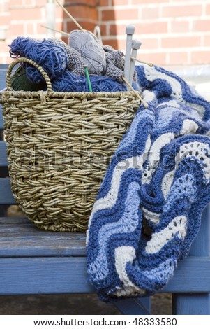 Blue wool and knitting needles in a wicker basket - stock photo