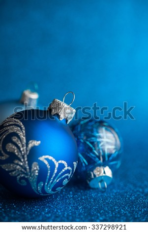 Blue xmas ornaments on dark blue glitter background with space for text. Merry christmas card. Winter holiday theme. Happy New Year. - stock photo