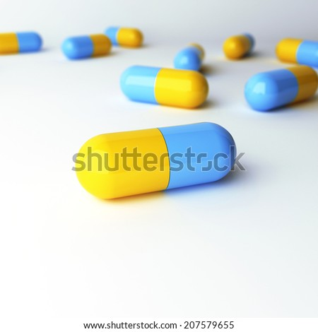 blue-yellow capsules with DOF on a white background - stock photo