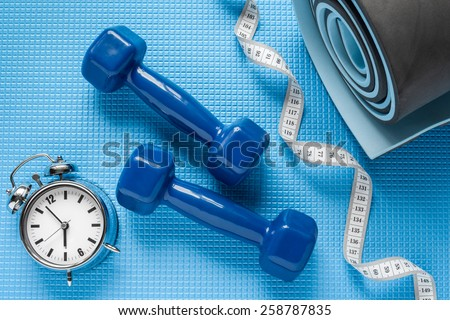 Blue yoga mat, two dumbbells, tape measure and alarm clock. - stock photo