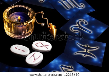blue zodiacal cards in circle around a candle, runes and magic pendulum - stock photo