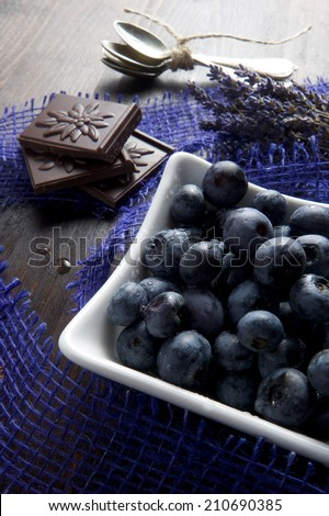 Blueberries and chocolate with lavender and spoon on wooden board - stock photo