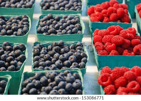 Blueberries and raspberries in box containers at a farmers market - stock photo