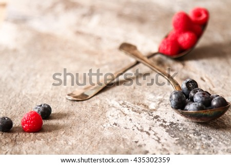 blueberries and raspberries on a metal spoon background gray stone - stock photo