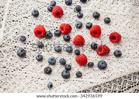 Blueberries and raspberries on a white lace tablecloth - stock photo