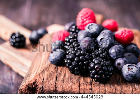 blueberries and raspberries on wooden background berry mix