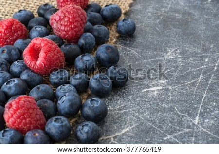 Blueberries and raspberries scattered on a jute cloth and chalkboard background - stock photo