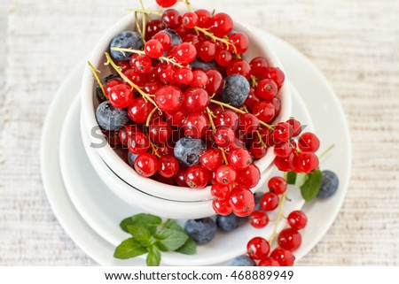 Blueberries and redcurrant in white bowl on a table