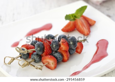 Blueberries and strawberries on a skewers - stock photo