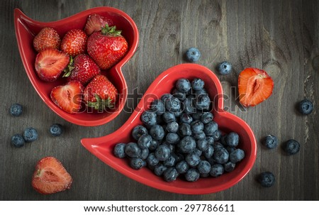 Blueberries and strawberry in heart plate on the table - stock photo