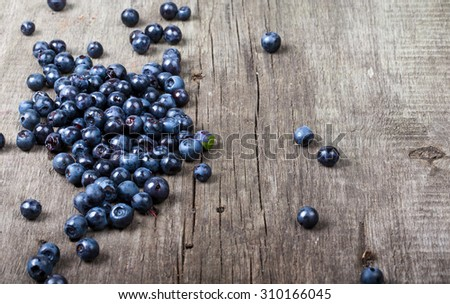blueberries collected manually scattered on the old board. - stock photo