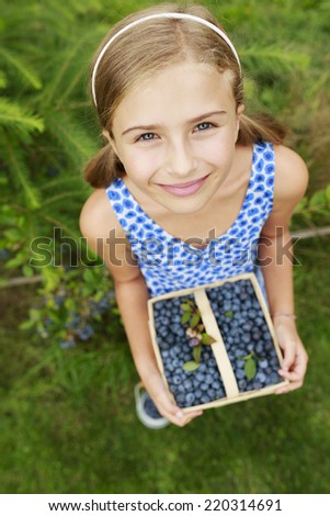 Blueberries, fruits - Lovely girl with picked fresh blueberries in the garden - stock photo