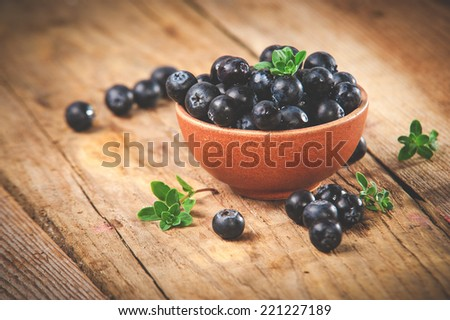 Blueberries in a bowl on a beautiful rustic table - stock photo