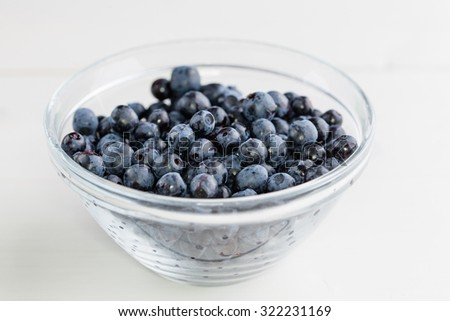 blueberries in a glasss-bowl on wooden table slightly above - stock photo