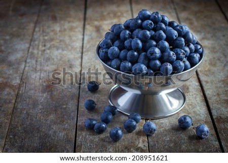 blueberries in a metal bowl on an old wooden background