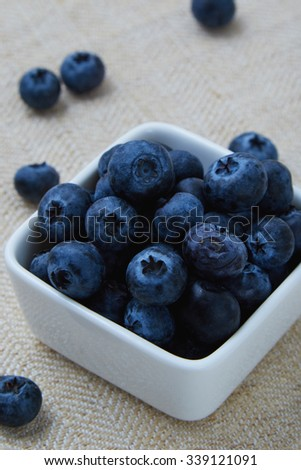 blueberries in a white bowl and on table
