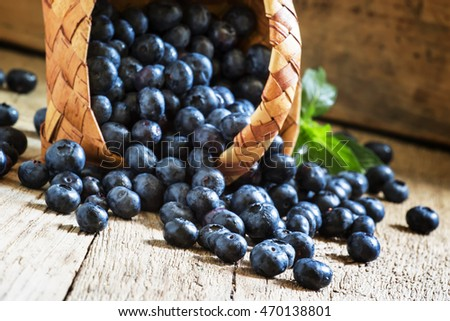 Blueberries in a wicker basket on the table, selective focus
