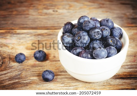 blueberries in the white bowl on a dark wood background. toning. selective focus on the middle of blueberries - stock photo
