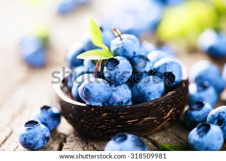 Blueberries in wooden bowl over rustic wooden table close up. Ripe and juicy fresh picked blueberry with green leaves. Berries harvest. Bilberries over wooden background. Berries. Diet concept - stock photo