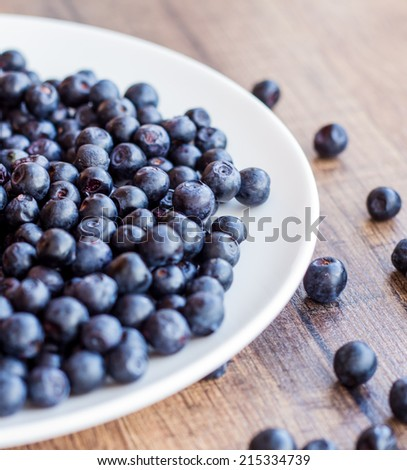 blueberries on a white plate wooden background