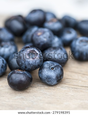 Blueberries on a wooden table, focus on a single blueberry, shallow DOF - stock photo