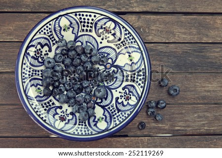 Blueberries on rustic plate on wooden table - stock photo