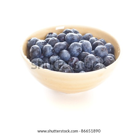 Blueberries spilling out of a pottery bowl - stock photo