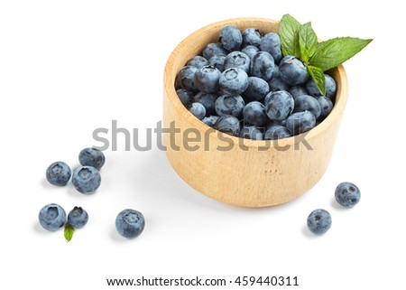 Blueberries with a green leaf in a wooden bowl on a white