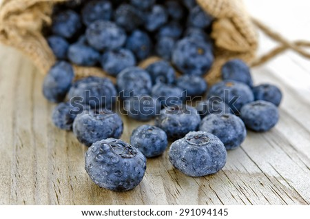blueberries with water droplets spilling out of burlap sack - stock photo