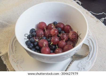 Blueberry and gooseberry in a plate with a spoon isolated on a black wooden table