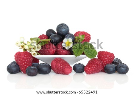 Blueberry and raspberry fruit in a porcelain dish with blueberry and raspberry flower and leaf sprigs, isolated over white background.