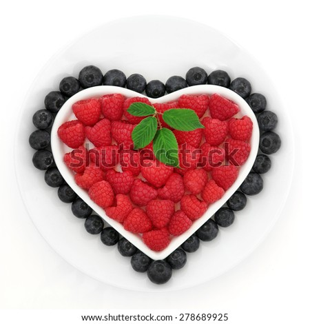 Blueberry and strawberry fruit in a heart shaped dish on a porcelain bowl over white background. - stock photo