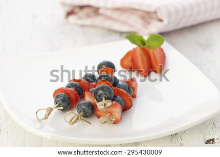 Blueberry and strawberry on a skewer - stock photo