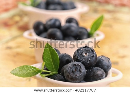 Blueberry. Blueberry  on wooden table background. Ripe fresh blueberries. Berries closeup. Healthy blueberry . Delicious fruits  - blueberry. Blueberry with greenn leaves, in bowl. - stock photo