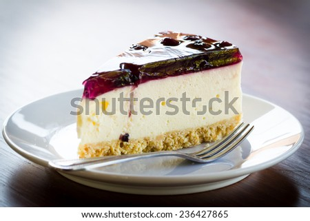 Blueberry cheesecake in white plate on wood table - stock photo