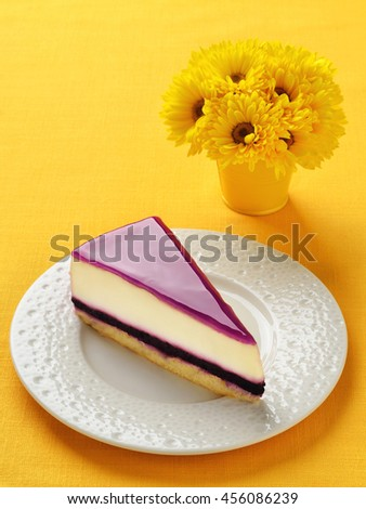 Blueberry cheesecake slice on plate. Yellow linen background. - stock photo