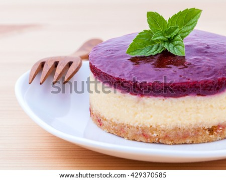Blueberry cheesecake with fresh mint leaves on wooden background. Selective focus depth of field. - stock photo