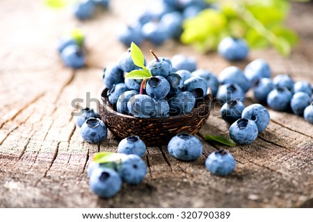Blueberry. Freshly picked blueberries over wooden table. Juicy and fresh blueberries with green leaves in wooden bowl. Rustic Background. Concept for healthy eating and nutrition - stock photo