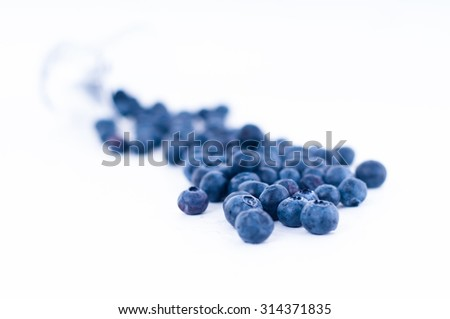 blueberry fruit fall from glass on white background - stock photo