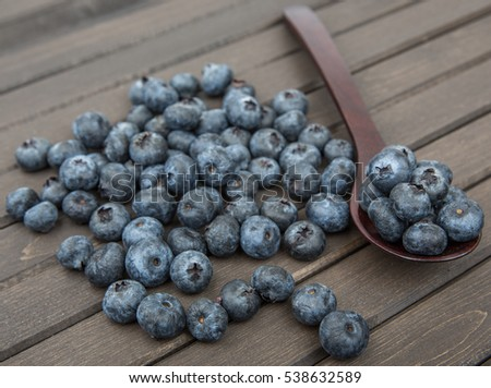 Blueberry fruits in a spoon over wooden background