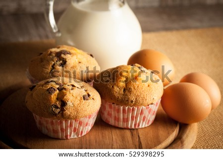 Blueberry home made muffins with cooking ingredients, eggs, milk, flour and fresh berries. Healthy breakfast concept of baked cupcakes.