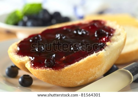 Blueberry jam on half a bun with a knife beside (Selective Focus, Focus on the front of the bun and jam)