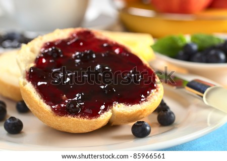 Blueberry jam on half a bun with fresh blueberries and other fruit and a cup in the back (Selective Focus, Focus on the left front of the jam and bun)