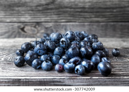 Blueberry  lie on wooden background. Rustic cozy background with healthy food. Fresh-gathered berries full of vitamins, good for diet nutrition and healthy meals.