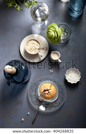Blueberry muffin and espresso at a cafe or at home, on dark background, top view. Modern country style setting and accessories. Toned photo. - stock photo