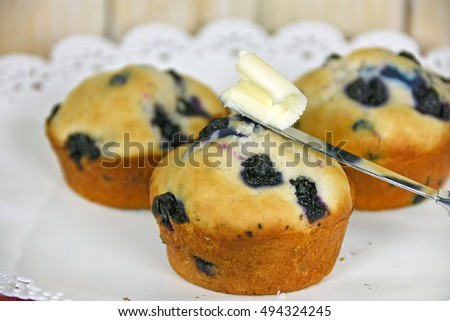 blueberry muffins with butter on knife