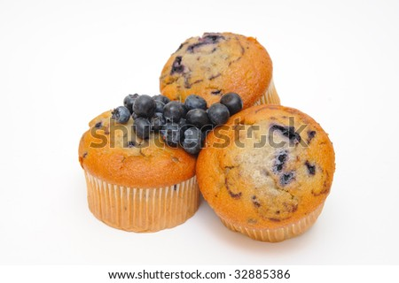 Blueberry muffins with fresh blueberries on top of the cakes on a light colored background. - stock photo