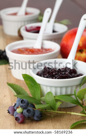 Blueberry, nectarine, black currant and gooseberry jams on a wooden board - stock photo